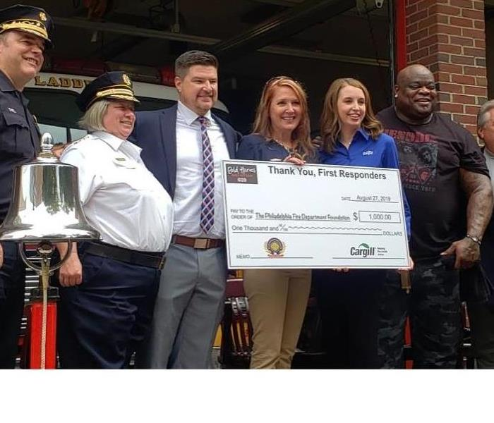 female accepting a check on behalf of The Philadelphia Fire Department Foundation